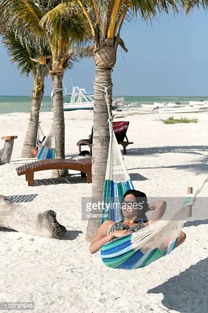 Belle jeune femme de détente dans un hamac sur une plage tropicale au paradis