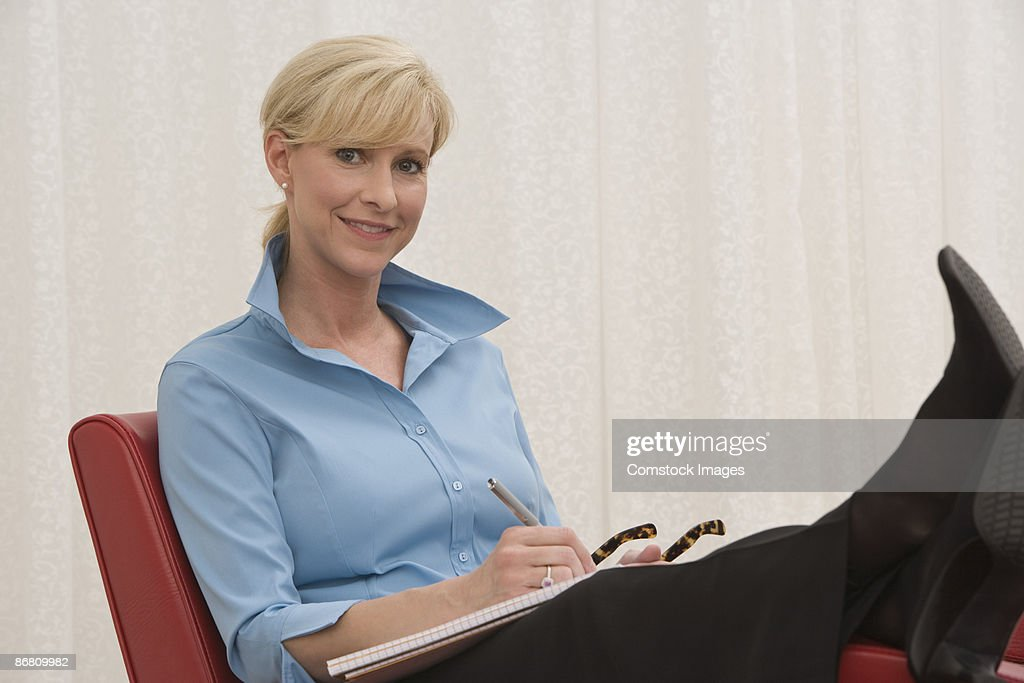 Relaxing businesswoman with paperwork : Stock Photo