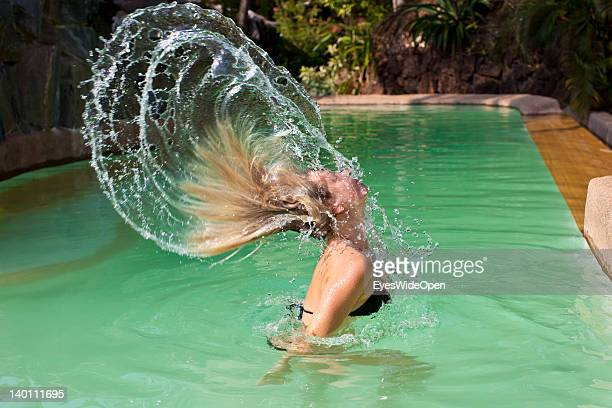 Relaxing holiday A woman throws her wet hair up in the air at a swimming pool at Yoga Magic Eco Retreat in Anjuna on February 1 2012 in Goa India