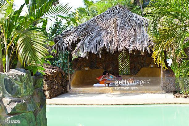 Relaxing holiday a young woman lies in a shady hut built from palmleaves and reading a book at the pool of Yoga Magic Eco Retreat in Anjuna on...