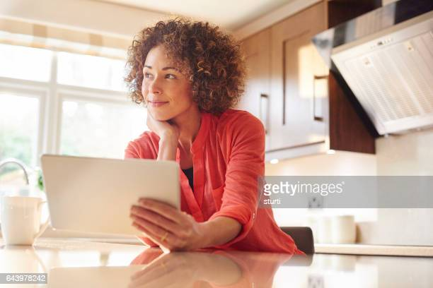 relaxing in her new kitchen with a tablet