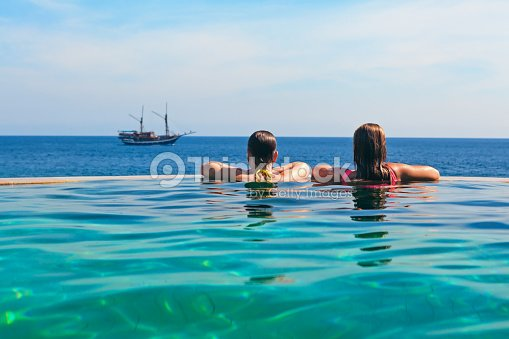 Relaxing in infinity swimming pool with sea view : Stock Photo
