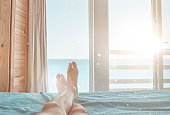 unrecognizable woman legs lying down in the bedroom and enjoying perfect view.