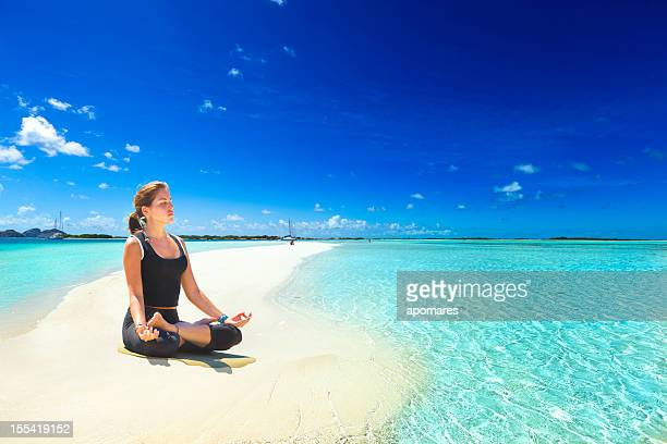 Relaxing in yoga lotus pose on tropical turquoise beach island