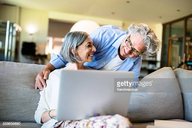 Relaxing mature couple doing shopping on line