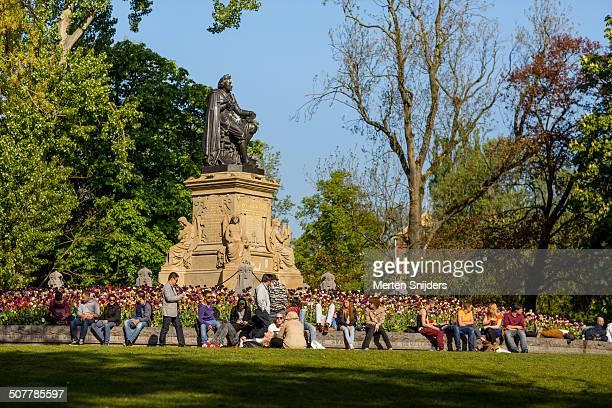 Relaxing people around Joost van Vondel statue