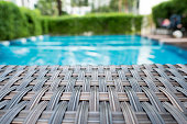 Relaxing rattan bed beside swimming pool with blur image of swimming pool and  green tree in background