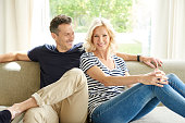 Full length shof a happy mature couple sitting on couch at home and relaxing togetherness.
