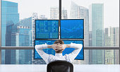 Rear view of a relaxing trader who is sitting in front of a trading station which consists of four screens with financial data. A concept of forex trading. Singapore panoramic view.