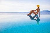 Young woman wearing a sun-hat enjoying sun