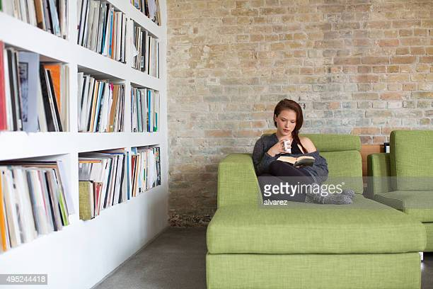 Relaxing young woman reading a book at home