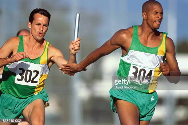 Relay race, competitor passing baton to team-mate