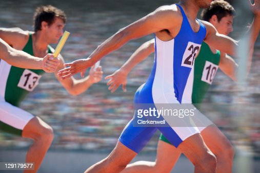 Relay race, male athletes passing relay baton