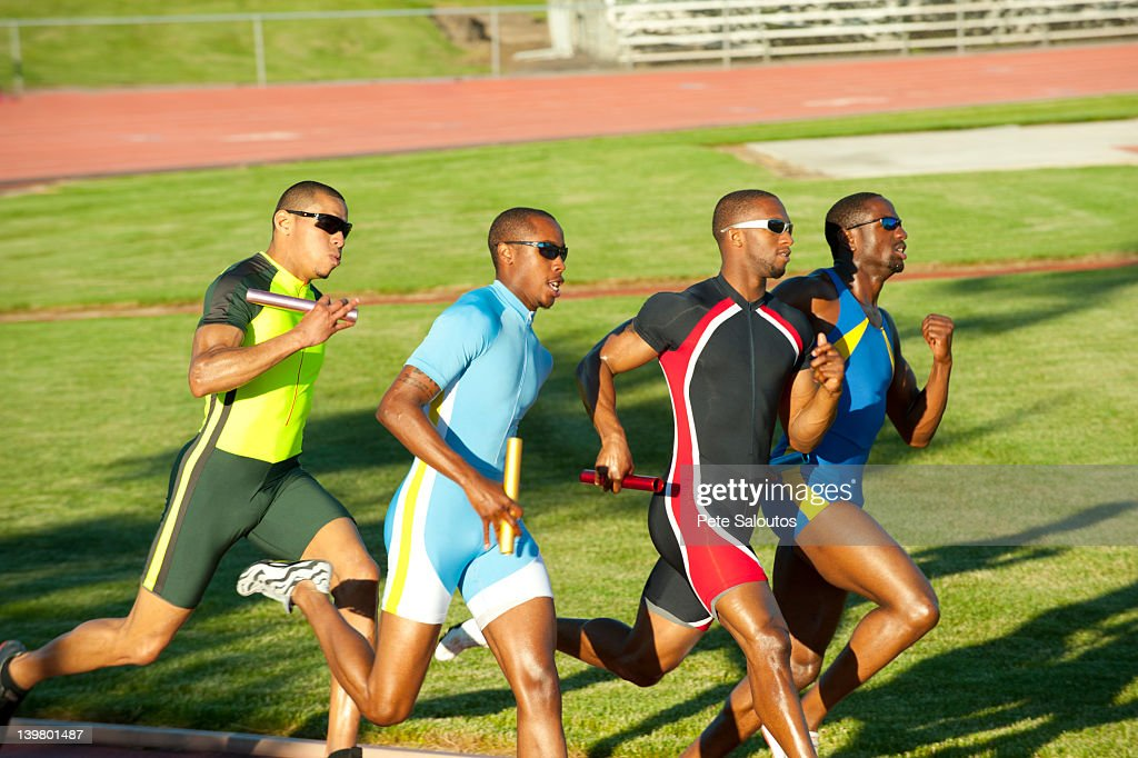 Relay racers running on track in race : Stock Photo