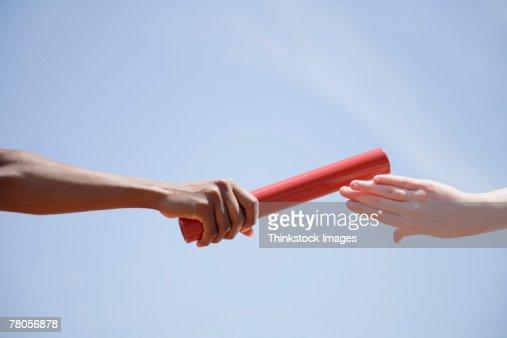 Relay runners' hands passing baton