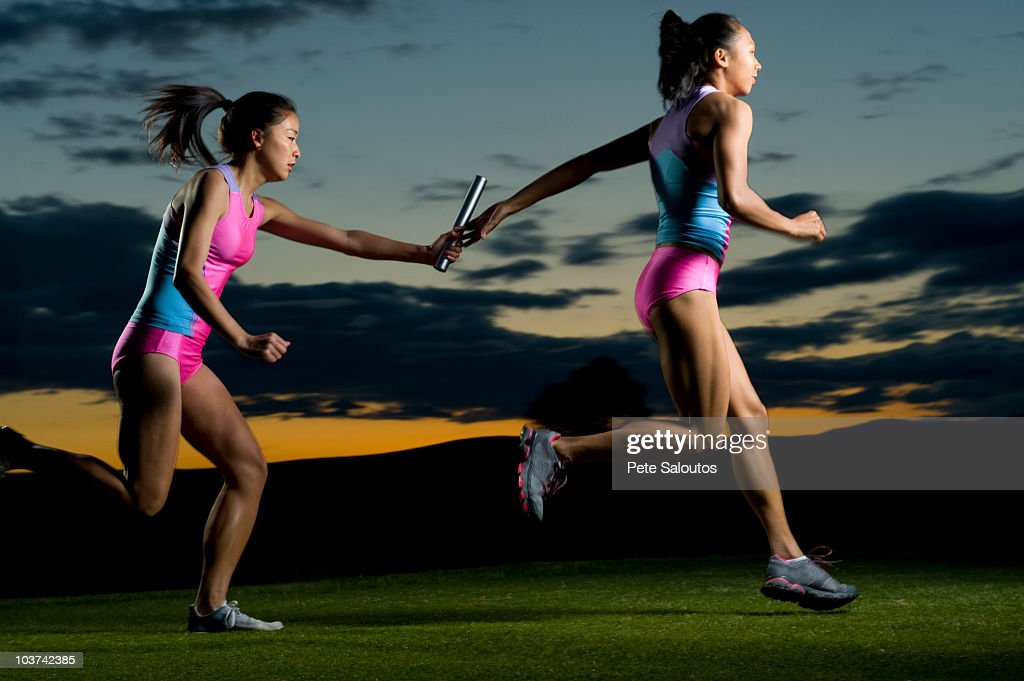 Relay runners passing baton in competition : Stock Photo