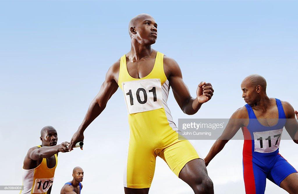 Relay Runners Passing Batons to Team Mates : Stock Photo