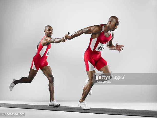 Relayers passing baton (studio shot)