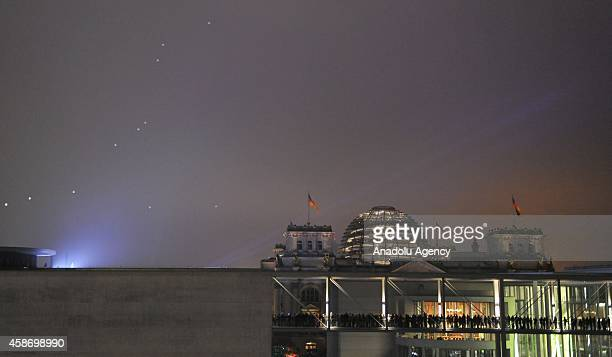 Released helium filled balloons are seen in the sky after people gather along the 15 kilometers line during the event named 'Lichtgrenze ' as part of...