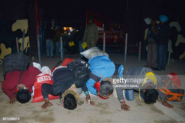 Released Indian fishermen prisoners kiss the ground after crossing the IndiaPakistan border at Wagah some 35kms west of Amritsar on January 6 after...