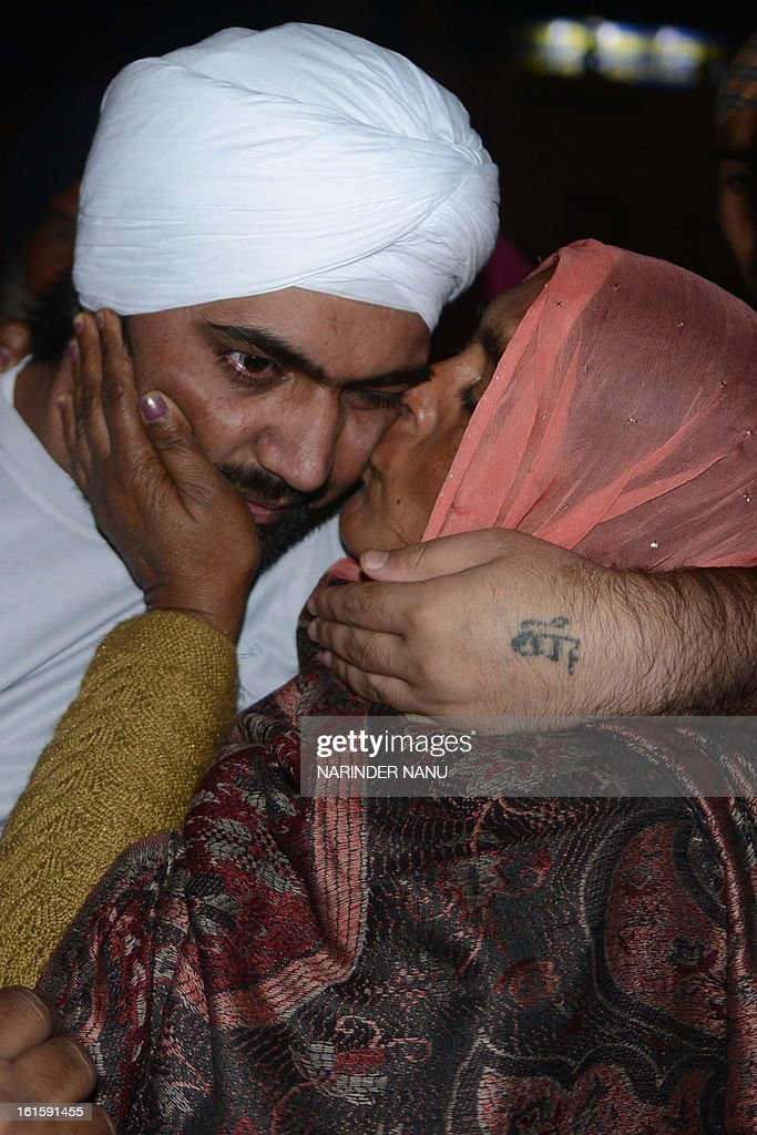 Released Indian prisoner Sukhjinder Singh (L) is greeted by his mother Jasbir Kaur (R) after his arrival outside the Sikh Shrine Golden temple in Amritsar on February 12, 2013. 17 Indian nationals on death row in the United Arab Emirates (UAE) have returned to Amritsar to pay their respects at the Sikh Shrine after paying blood money to the family of a Pakistan,Misri Nazir, in the UAE .