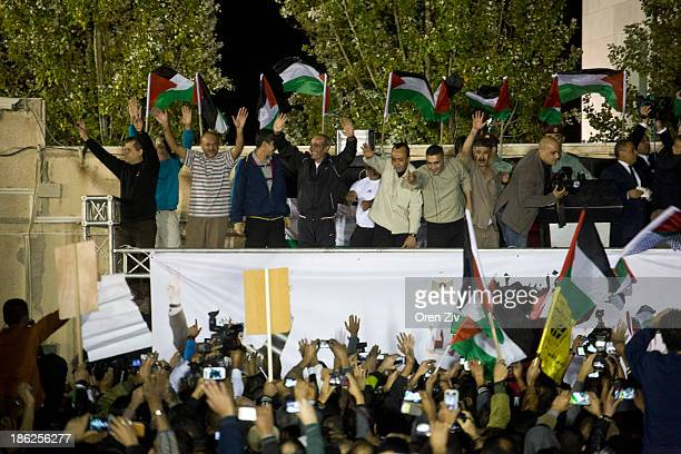 Released Palestinian prisoners stand on a sage as they arrive to the Mukata Presidential Compound in the early morning hours on October 30 2013 in...