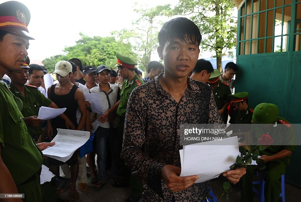 A released prisoner (C) holds a rose and an amnesty certificate as he leaves the Hoang Tien prison in Chi Linh district, northern province of Hai Duong on August 30, 2013. Vietnam will free more than 15,000 convicts to mark its independence day celebrations, the president's office said on August 29, in a major amnesty that excludes prominent political prisoners. AFP PHOTO/HOANG DINH Nam