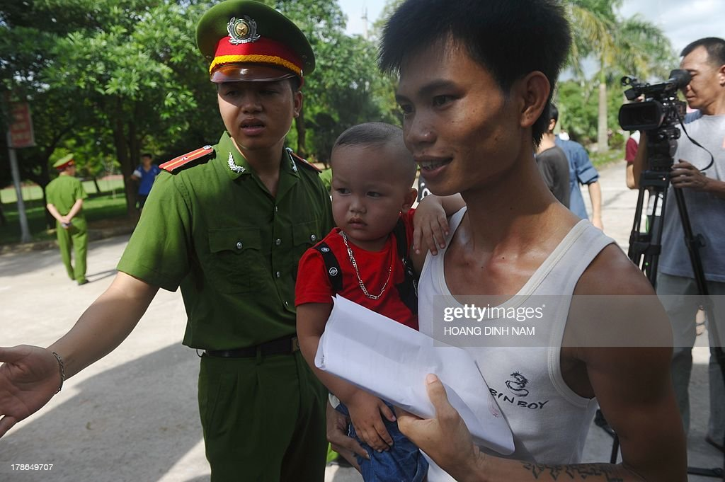 A released prisoner (C) holds his son as he leaves the Hoang Tien prison in Chi Linh district, northern province of Hai Duong on August 30, 2013. Vietnam will free more than 15,000 convicts to mark its independence day celebrations, the president's office said on August 29, in a major amnesty that excludes prominent political prisoners. AFP PHOTO/HOANG DINH Nam