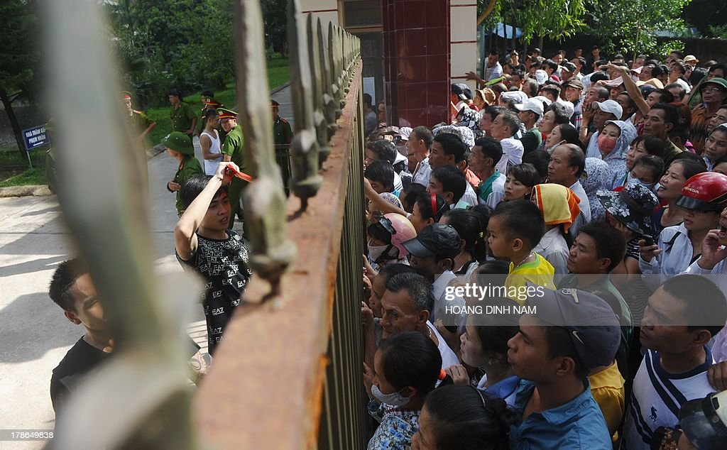 Released prisoners (L) look for relatives amongst families waiting outside a gate at the Hoang Tien prison in Chi Linh district, northern province of Hai Duong on August 30, 2013. Vietnam will free more than 15,000 convicts to mark its independence day celebrations, the president's office said on August 29, in a major amnesty that excludes prominent political prisoners. AFP PHOTO/HOANG DINH Nam