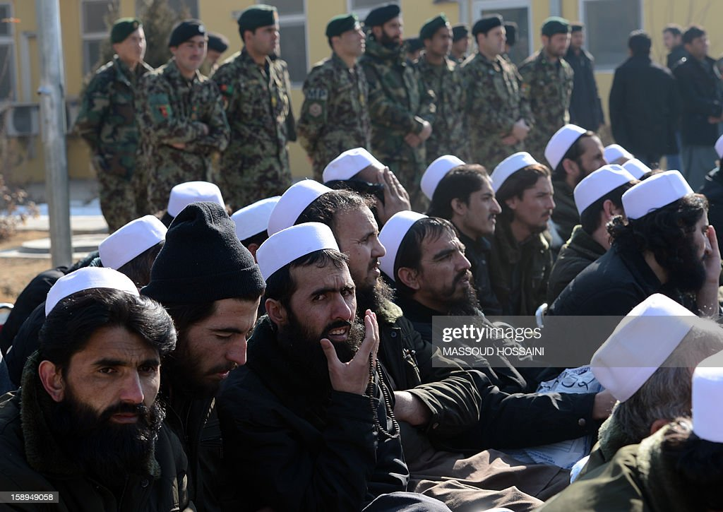 Released Taliban prisoners sit on chairs as they listen during a ceremony in Pul-e-Charkhi jail on the outskirts of Kabul on January 4, 2013. With tears streaming down their rugged faces, scores of Afghan prisoners embraced waiting relatives and walked to freedom -- the latest government move to foster reconciliation after 11 years of war. The 80 men, all wearing white skull caps, were released on Friday at a ceremony held inside Pul-e-Charkhi, Afghanistan's largest prison located on dusty flat lands east of the capital Kabul. AFP PHOTO/ Massoud HOSSAINI