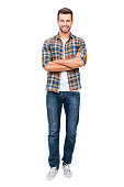 Full length of smiling young man keeping arms crossed and looking at camera while standing against white background