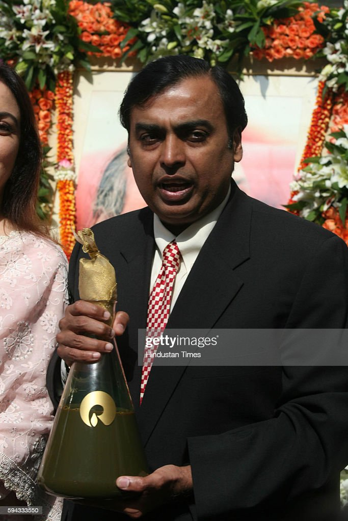 Reliance Industries chairman and managaing director Mukesh ambani and his wife Neeta ambani display the first bottle of Crude oil production from the...
