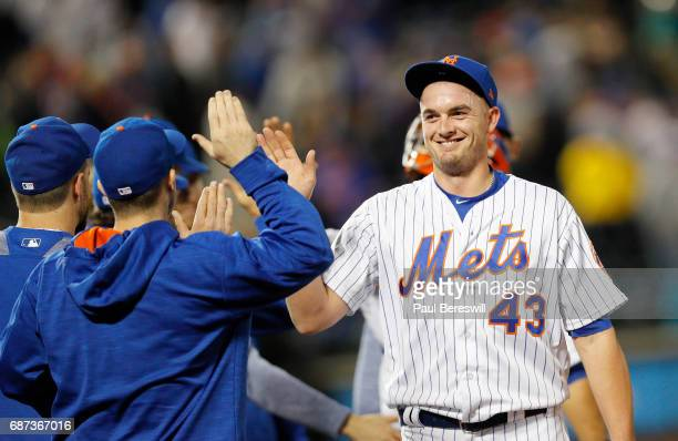 Relief pitcher Addison Reed of the New York Mets is all smiles as he gets high fives from teammates after closing out the Mets 75 win in an...