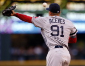 Relief pitcher Alfredo Aceves of the Boston Red Sox attempts to catch a line drive by Dustin Ackley of the Seattle Mariners in the third inning at...