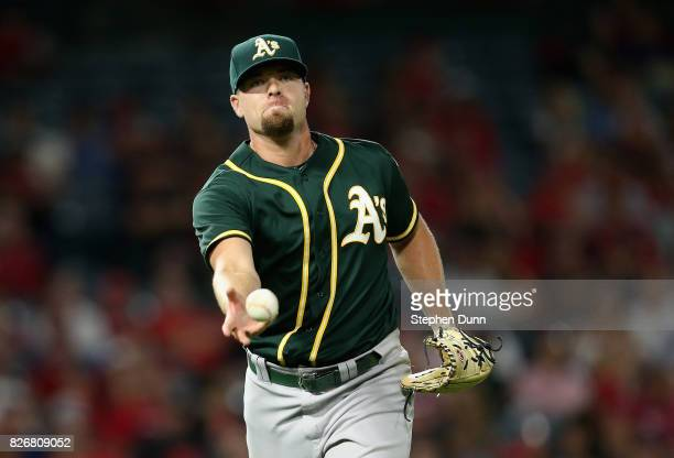 Relief pitcher Blake Treinen of the Oakland Athletics flips the ball to first afte fielding a grounder to get Albert Pujols of the Los Angeles Angels...