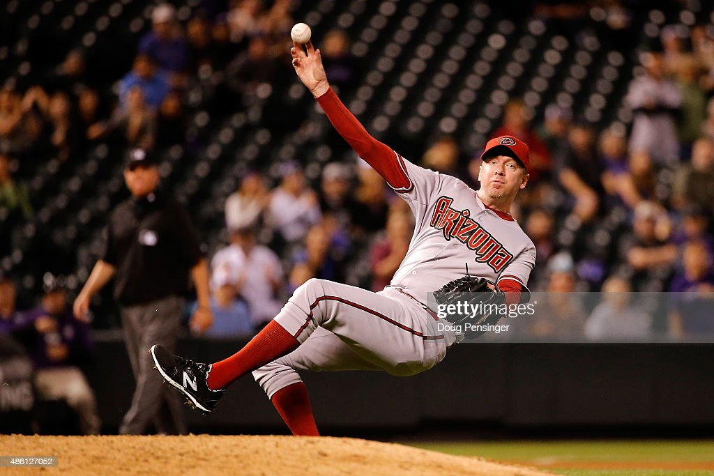 Relief pitcher Brad Ziegler of the Arizona Diamondbacks makes a throwing error after fielding a ground ball by DJ LeMahieu of the Colorado Rockies in...