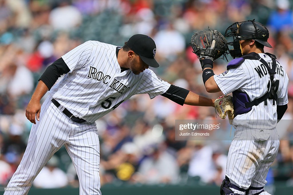 Relief pitcher Carlos Esteves #54 of the Colorado Rockies pushes catcher Tony Wolters #14 away from the mound during the ninth inning against the Toronto Blue Jays at Coors Field on June 29, 2016 in Denver, Colorado. The Blue Jays defeated the Rockies 5-3.