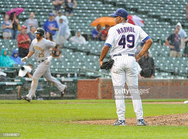 Relief pitcher Carlos Marmol of the Chicago Cubs stands on the mound as Derrick Lee of the Pittsburgh Pirates rounds the bases after hitting a grand...
