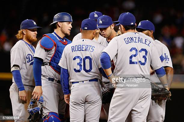 Relief pitcher Casey Fien of the Los Angeles Dodgers talks with manager Dave Roberts on the mound during the 12th inning of the MLB game against the...
