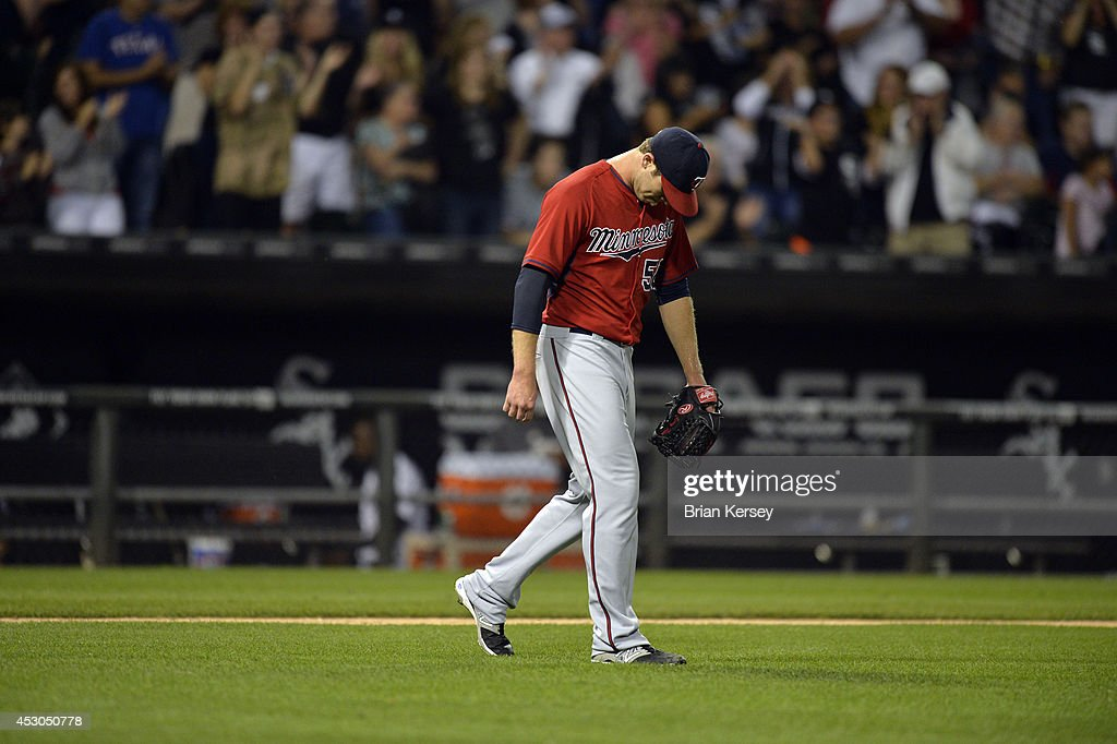 Relief pitcher Casey Fien #50 of the Minnesota Twins hangs his head after giving up an RBI single to Alexei Ramirez #10 of the Chicago White Sox scoring Jose Abreu during the eighth inning at U.S. Cellular Field on August 1, 2014 in Chicago, Illinois.