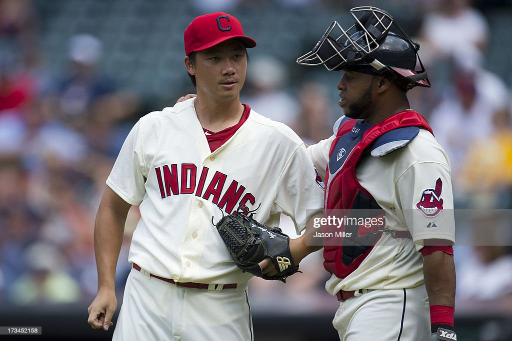 Relief pitcher C.C. Lee #20 talks with catcher Carlos Santana #41 of the Cleveland Indians during the fifth inning against the Kansas City Royals at Progressive Field on July 14, 2013 in Cleveland, Ohio.