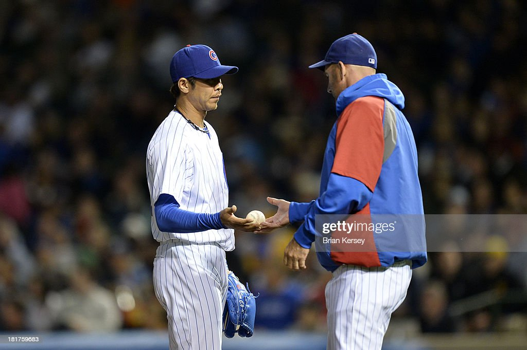 Relief pitcher Chang-Yong Lim #12 (L) hands the ball to manager Dale Sveum #4 of the Chicago Cubs as he is relieved during the fifth inning against the Pittsburgh Pirates at Wrigley Field on September 24, 2013 in Chicago, Illinois.