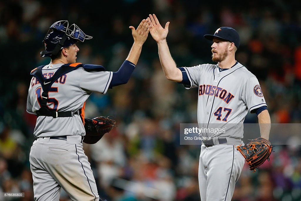 Relief pitcher Chris Devenski #47 of the Houston Astros is congratulated by catcher Jason Castro #15 after beating the Seattle Mariners 7-3 at Safeco Field on July 15, 2016 in Seattle, Washington.