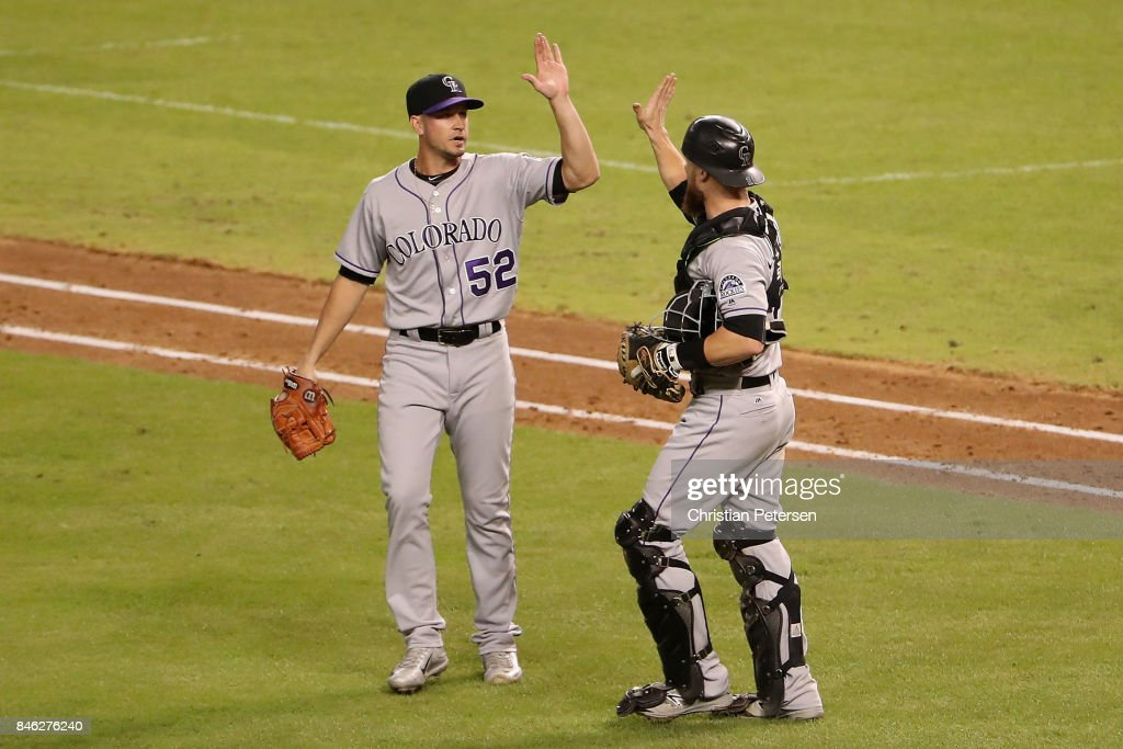 Relief pitcher Chris Rusin #52 of the Colorado Rockies celebrates with catcher Jonathan Lucroy #21 after defeating the Arizona Diamondbacks 4-2 in the MLB game at Chase Field on September 12, 2017 in Phoenix, Arizona.