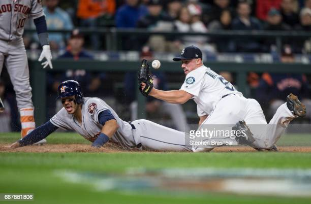 Relief pitcher Dan Altavilla of the Seattle Mariners juggles the baseball as Carlos Correa of the Houston Astros slides safely into home plate after...