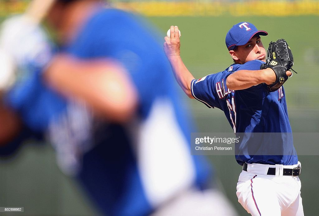 Relief pitcher Derek Holland of the Texas Rangers pitches against the Kansas City Royals during the spring training game at Surprise Stadium on March...