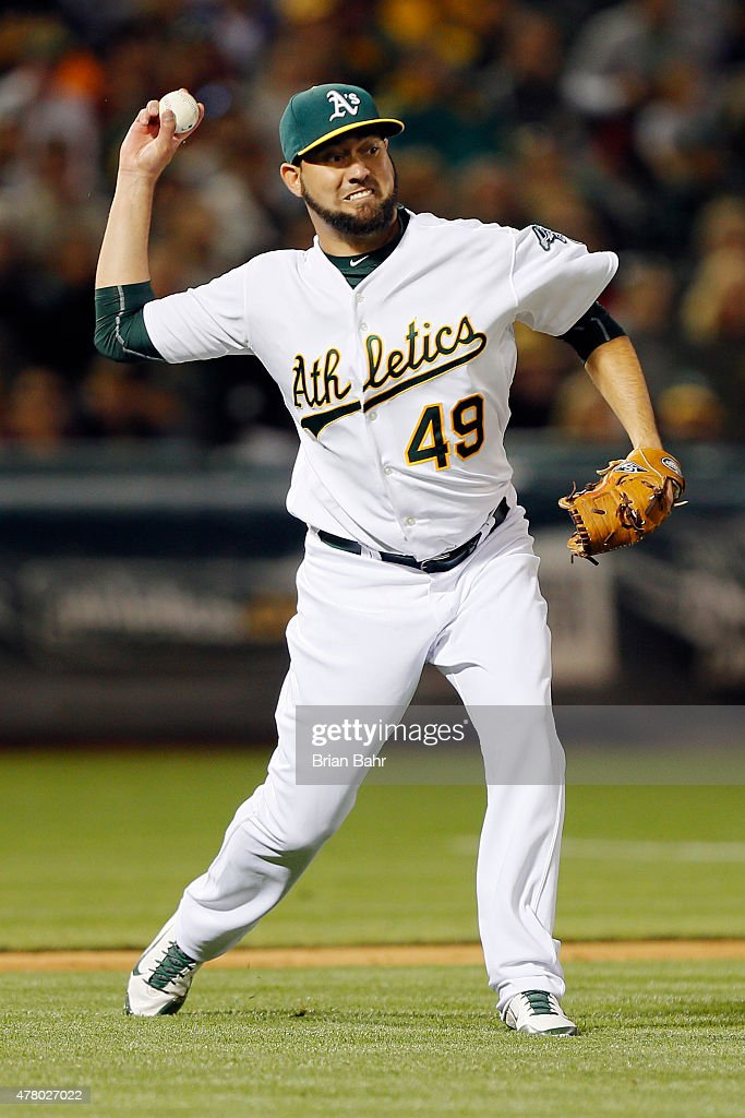 Relief pitcher Edward Mujica of the Oakland Athletics makes an errant throw to first base for an error on a bunt single by Erick Aybar of the Los...
