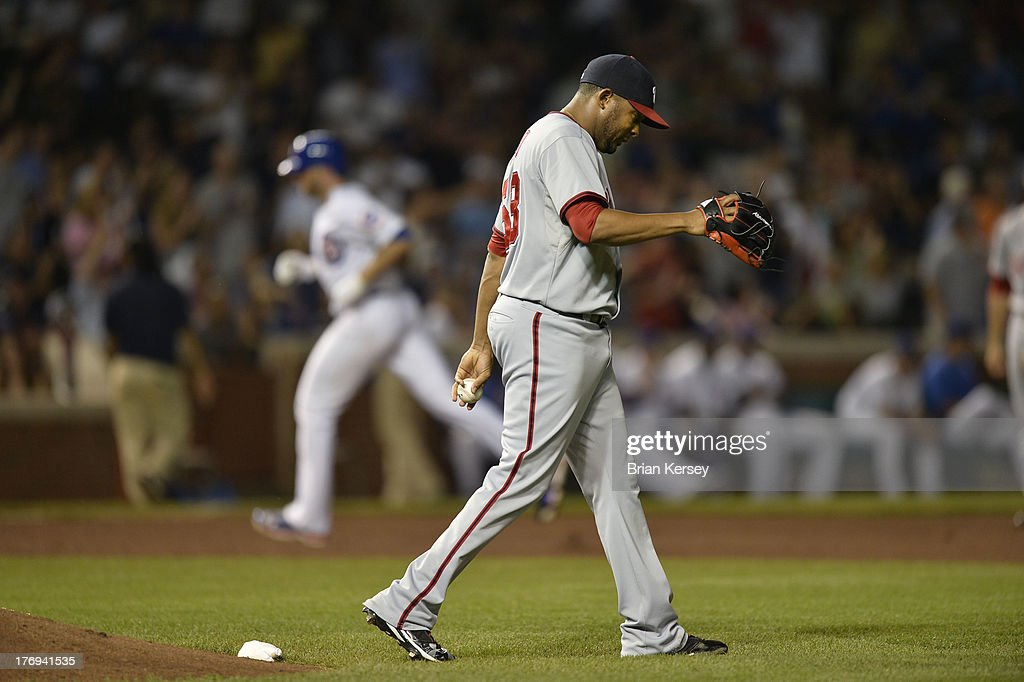 Relief pitcher <a gi-track='captionPersonalityLinkClicked' href=/galleries/search?phrase=Fernando+Abad&family=editorial&specificpeople=6767746 ng-click='$event.stopPropagation()'>Fernando Abad</a> #58 of the Washington Nationals walks on the field as <a gi-track='captionPersonalityLinkClicked' href=/galleries/search?phrase=Nate+Schierholtz&family=editorial&specificpeople=803208 ng-click='$event.stopPropagation()'>Nate Schierholtz</a> #19 of the Chicago Cubs rounds the bases after hitting a two-run home run scoring Dioner Navarro #30 during the seventh inning at Wrigley Field on August 19, 2013 in Chicago, Illinois.