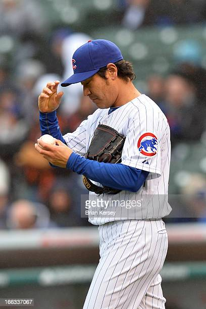 Relief pitcher Hisanori Takahashi of the Chicago Cubs looks at the ball during the fifth inning against the San Francisco Giants at Wrigley Field on...