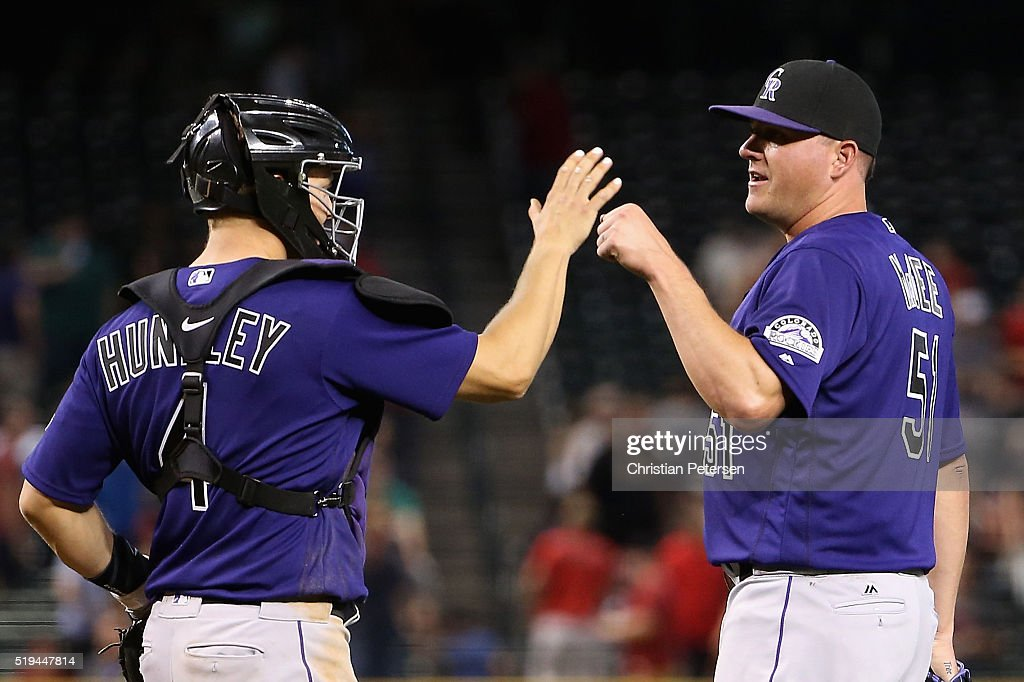Relief pitcher Jake McGee #51 of the Colorado Rockies high-fives catcher Nick Hundley #4 after defeating the Arizona Diamondbacks 4-3 in the MLB game at Chase Field on April 6, 2016 in Phoenix, Arizona.